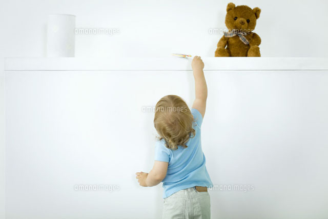 Toddler reaching for lollipop on high shelf,rear view