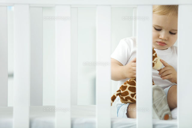 Toddler sitting in crib,playing with stuffed giraffe