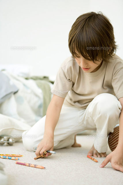 Boy crouching on floor,picking up colored pencils