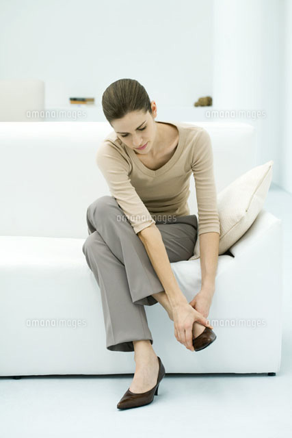 Woman sitting on sofa,putting on shoe,full length