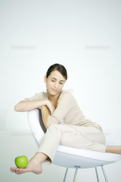 Woman lounging in chair,balancing apple on foot