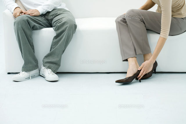Man and woman sitting on sofa,woman putting on shoe