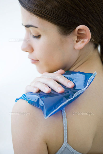 Woman placing cold compress on shoulder,close-up
