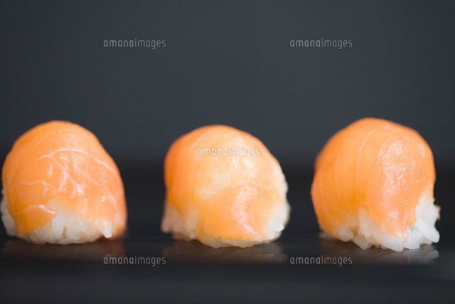 Three pieces of salmon nigiri sushi with dark background
