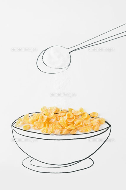Spoon sprinkling sugar on bowl of cereal
