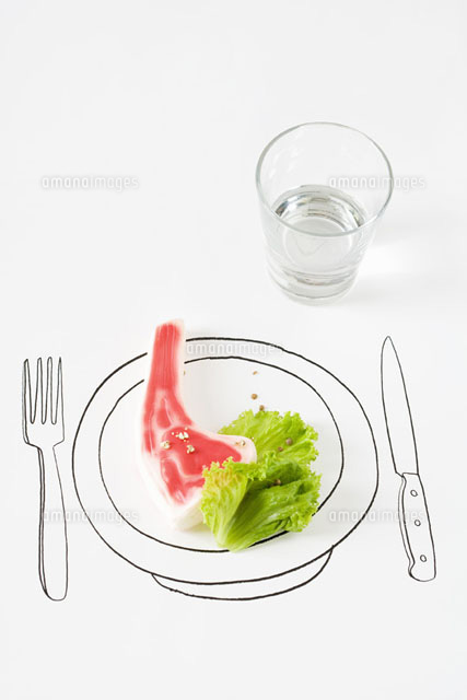 Plastic steak and lettuce on drawing of plate