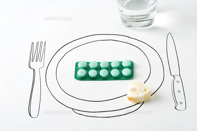 Blister pack of pills and small piece of bread on plate