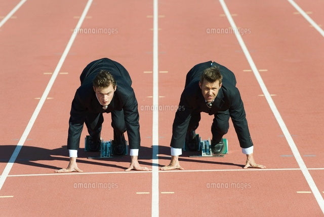 businessmen crouched in starting position on running track