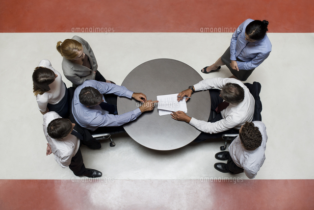 businessmen flanked by support staff negotiate contract 11001059889