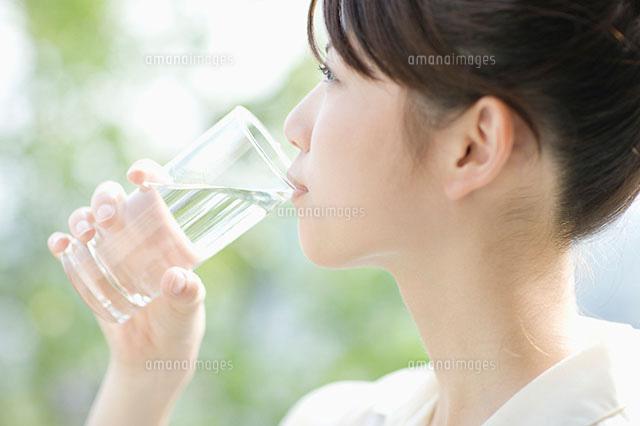 コップで水を飲む女性[110040743...