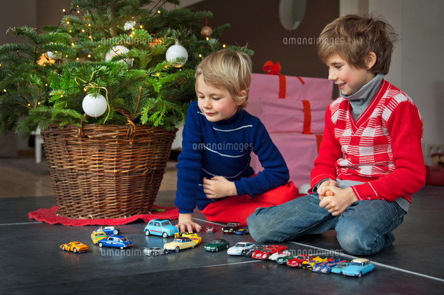 Two boys playing with Christmas presents