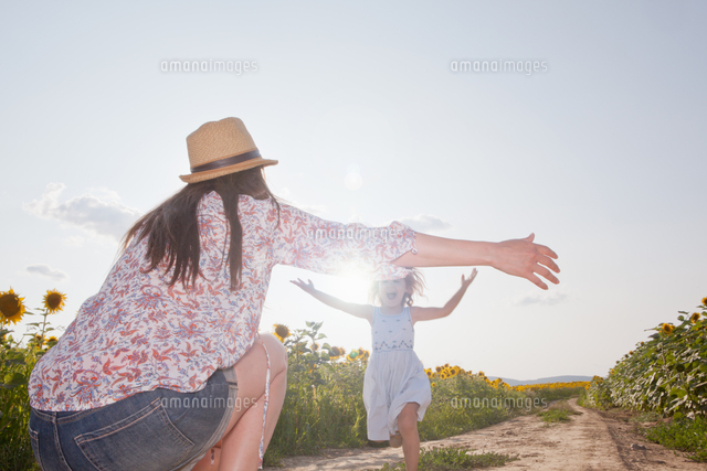 girl running through field to mother with open arms 11015237601