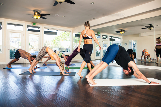 yoga instructor in class with people in downward dog position