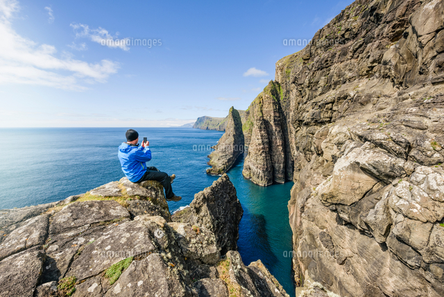 man on rocks photographing ocean vagar faroe islands 11015287581