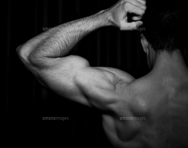 rear view of bare chested man flexing bicep muscles 11015296601