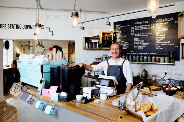 portrait of male business owner behind counter of independent coffee