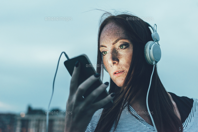 young freckled woman listening to headphones looking at smartphone