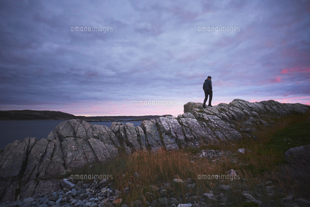 hiker hiking on rocks at dusk fogo island newfoundland canada