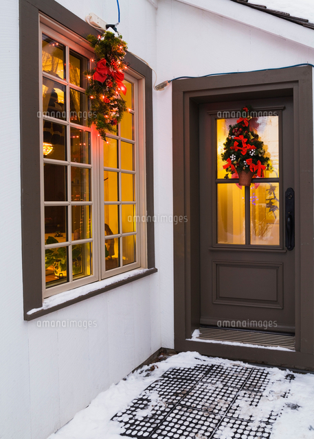 window and brown front entrance door with christmas lights and