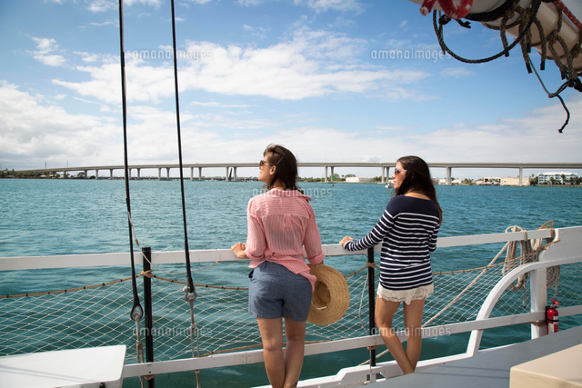 two women standing on deck of sailing boat looking at view rear