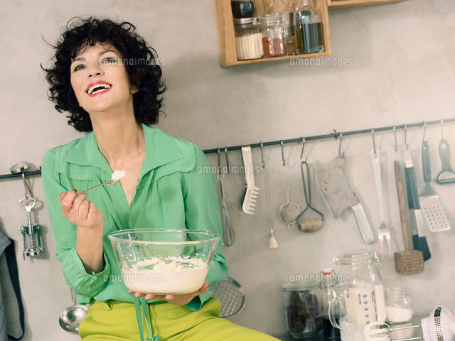 woman in kitchen with mixing bowl throwing head back laughing