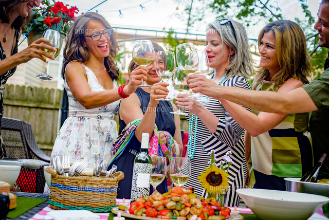 group of people at garden party holding wine glasses making a