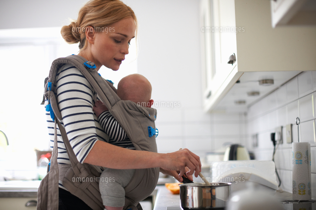 woman cooking in kitchen baby strapped to body in sling 11015327595