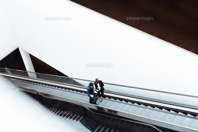 Businessman and businesswoman with wheeled luggage on escalator in hotel building
