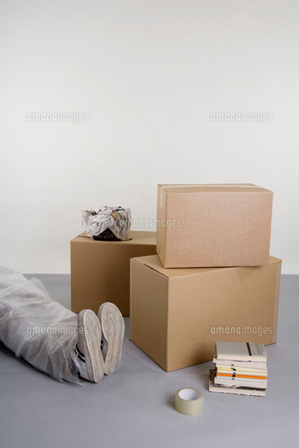 stacked boxes and books and a body wrapped in bubble wrap