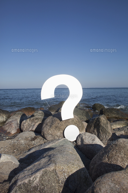 question mark symbol on rocks by sea against clear blue sky