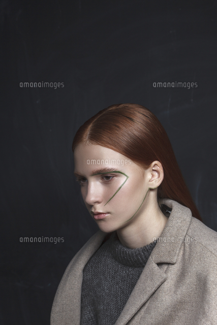 thoughtful teenage girl wearing jacket with face paint against black