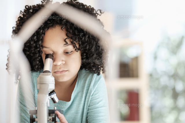 african american girl using microscope in science classroom