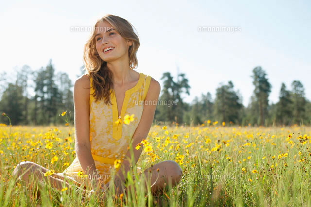 Woman sitting in wildflower field