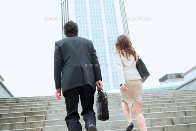 階段を上るビジネスマンとビジネ...