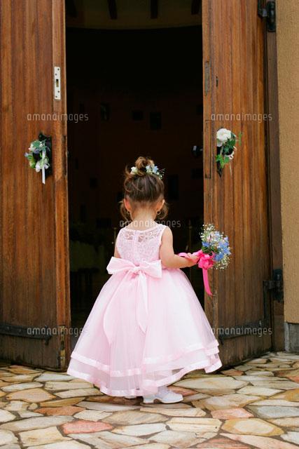 ドアの前に立つドレスを着た女の子の後姿[11038000778]| 写真素材・ストックフォト・画像・イラスト素材|アマナイメージズ