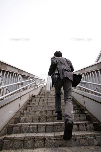 階段を上るスーツ姿の男性[11038...