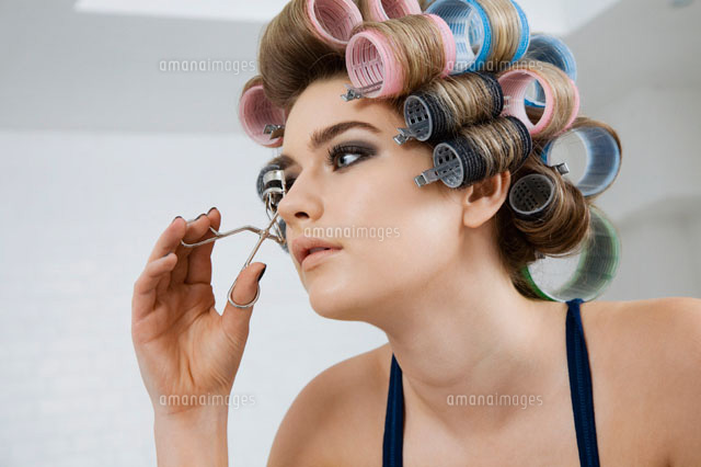 model in hair curlers using eyelash curler 11044009271 写真素材