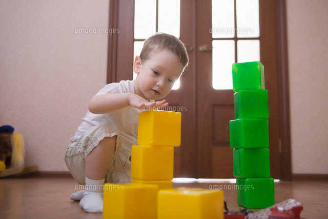 Young boy plays with green and yellow building bricks