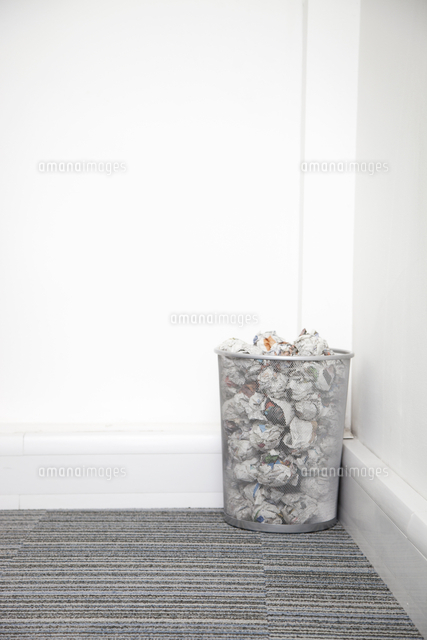 wastebasket full of crumpled paper in corner against white w