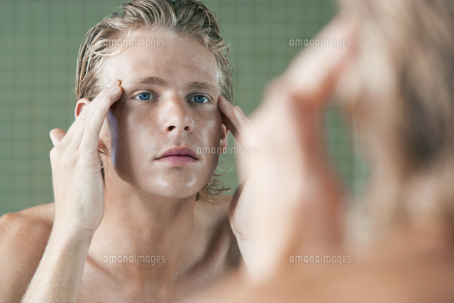 Man rubbing temples in front of mirror