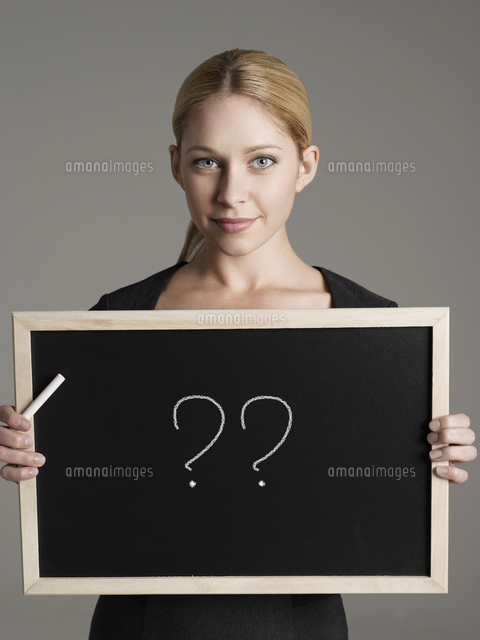 Portrait of young businesswoman holding blackboard with ques