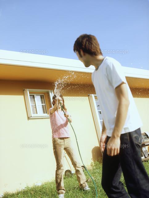水をかけ合うカップル[110700358...