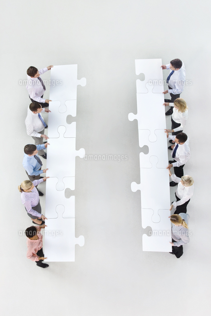 business people standing face to face in rows and holding large