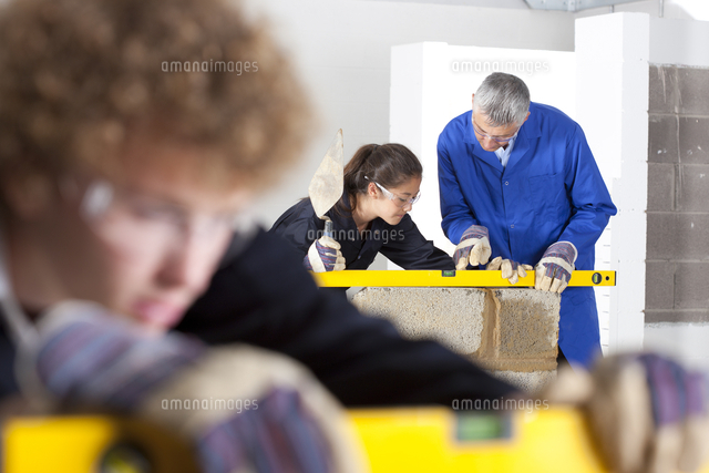 teacher talking to student using level in bricklaying vocational