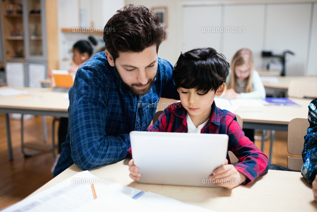 teacher assisting male student in using digital tablet while sitting