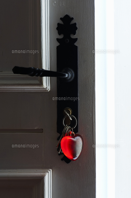 bunch of keys with heart shaped key fob in old open front door