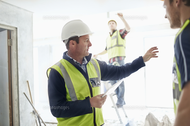 foreman with digital tablet gesturing to construction worker at