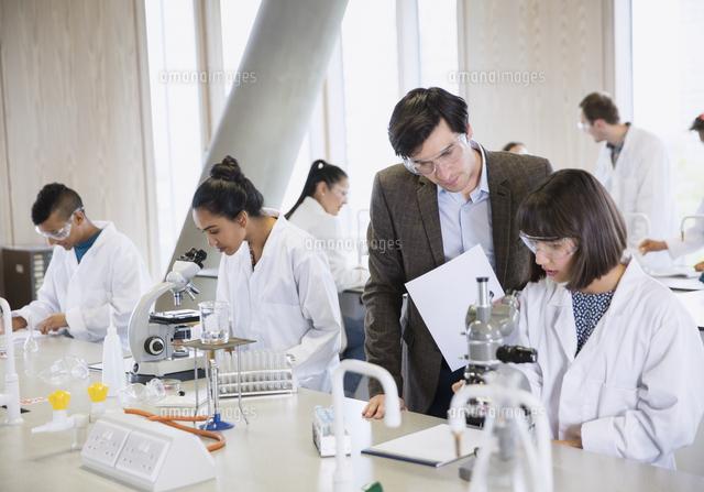 science professor helping college student conducting scientific