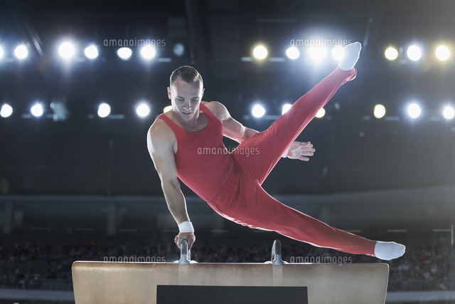 male gymnast performing on pommel horse in arena 11086031785 写真
