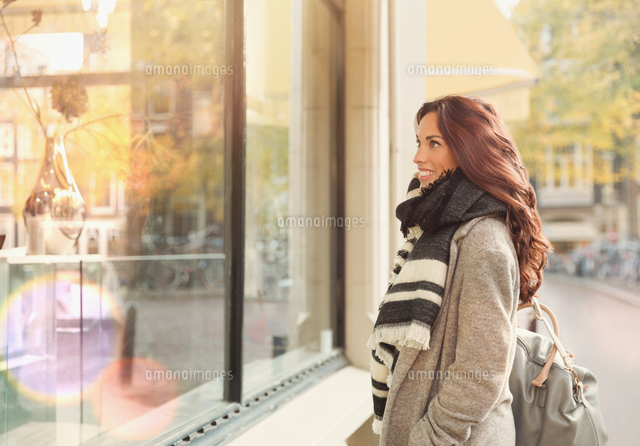 smiling young woman window shopping at urban storefront 11086033432